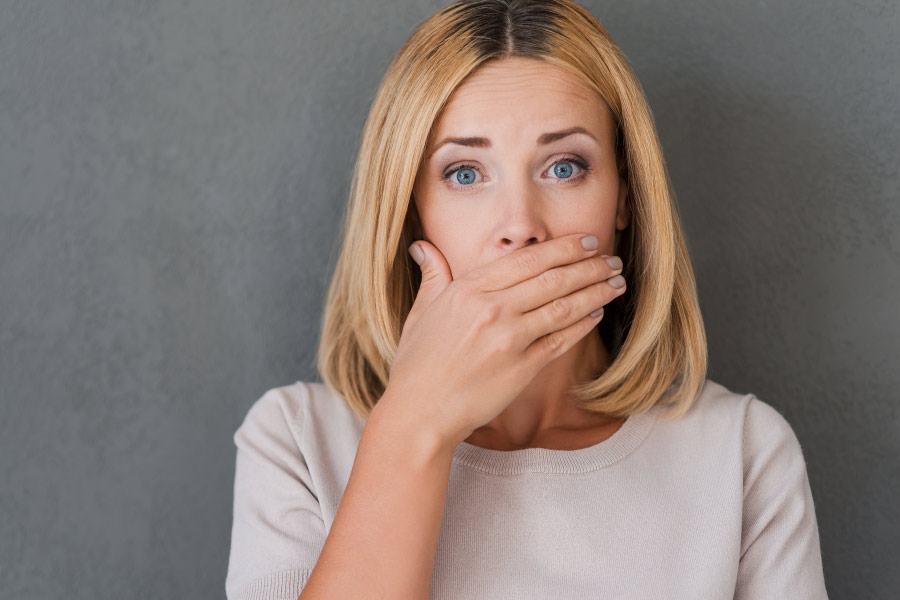 Blonde haired, blue-eyed woman covers her mouth for fear of bad breath