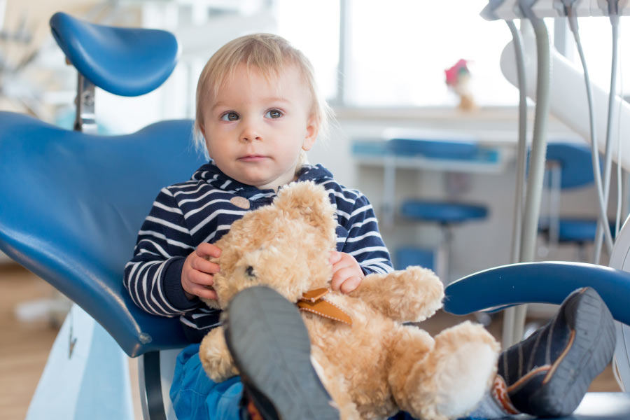 Little blonde boy and his teddy bear in the dental chair.