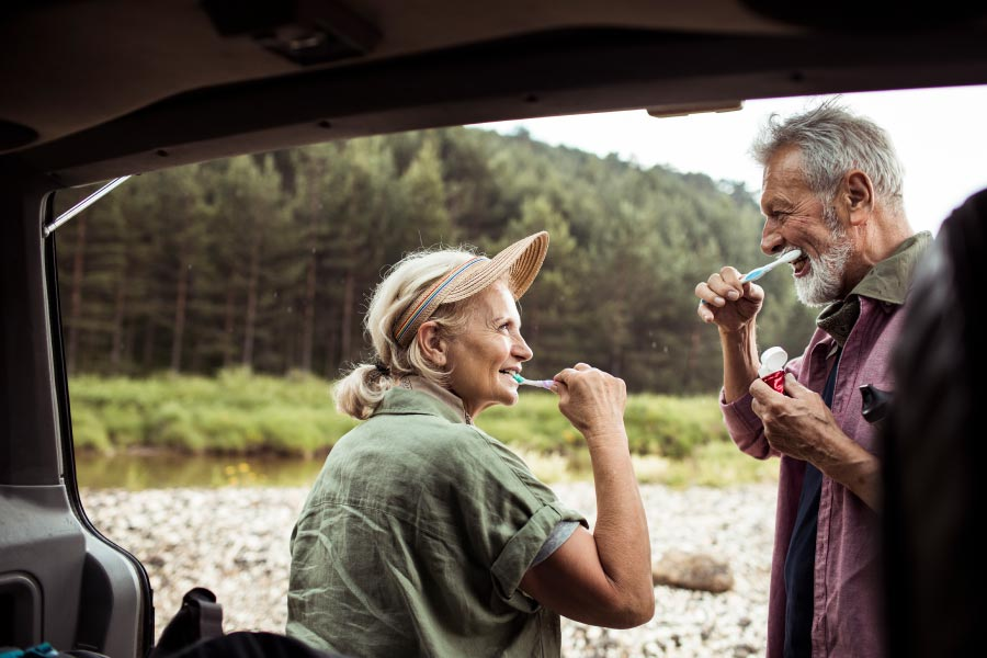Senior couple brushing their teeth near their SUV while camping.