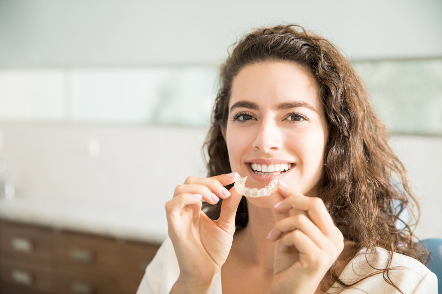 Middle aged brown haired woman smiling while holding a clear Invisalign aligner.
